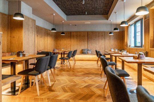 Heller Frühstücksraum mit Parkettboden und Wandgestaltung aus Holz
