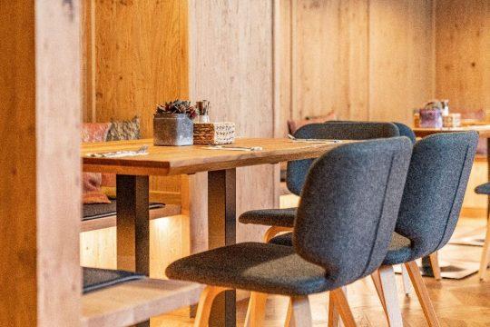 Frühstücksraum mit hellem Holz und gefilzten Stühlen