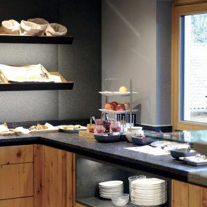 Frühstücksbuffet mit abgehängter Decke, Spots und Schränken mit indirekter Beleuchtung